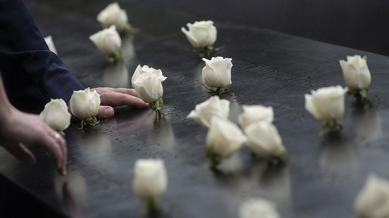 Two people have each placed a hand on a bronze parapet at the Memorial. They are next to about a dozen white roses that have been placed at the names of victims.