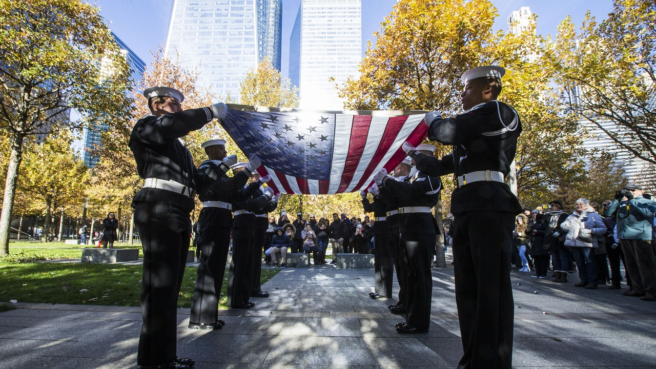 Members of the U.S. Navy hold a flag-folding ceremony on the 9/11 Memorial plaza before a group of onlookers.