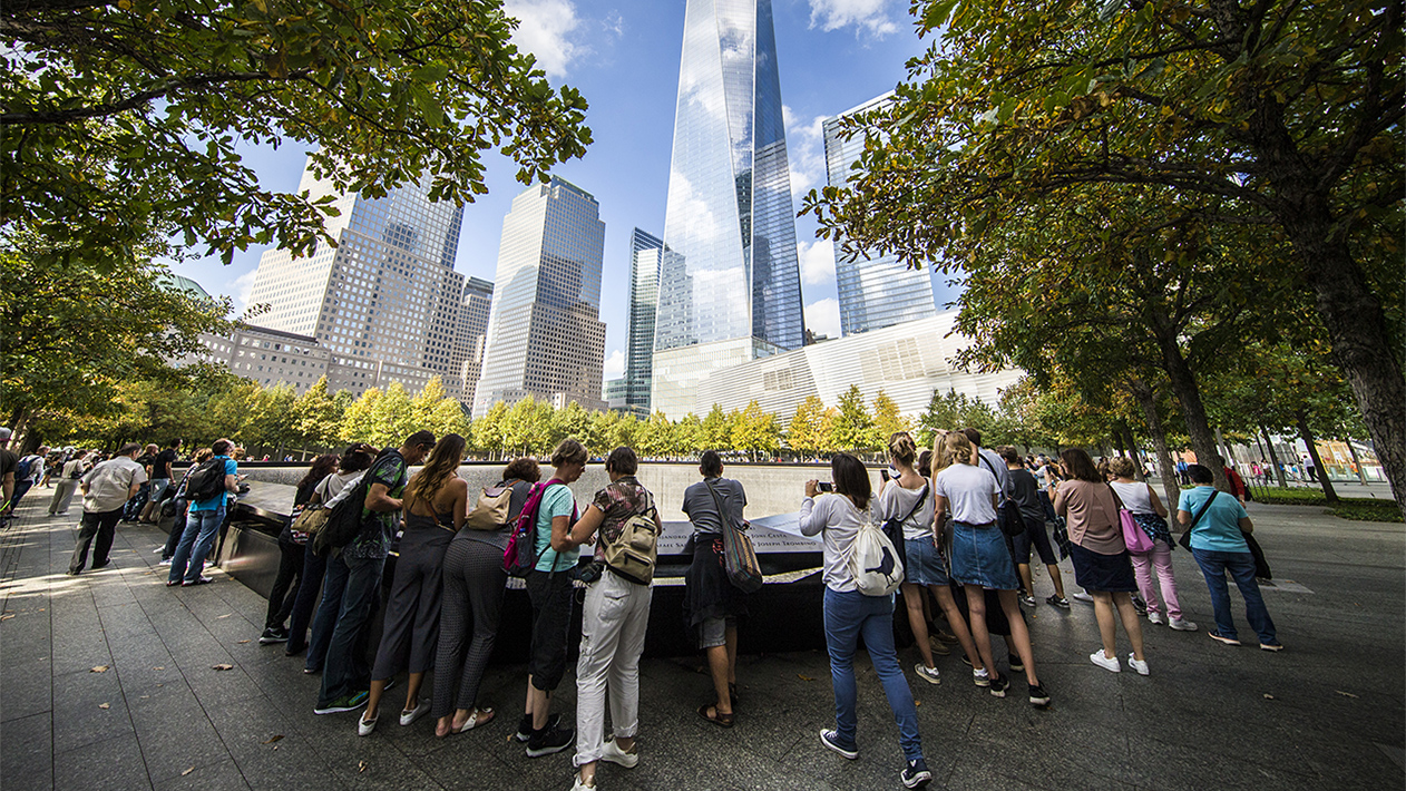 A group of students visits the 9/11 Memorial on a sunny day.
