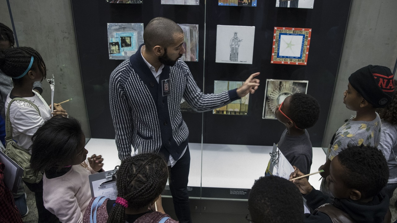 A tour guide points to pictures in a display case as he leads a group of middle school students through the Museum. The students have pencils and clipboards.