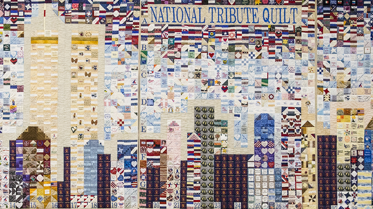 "A mosaic quilt forms the Twin Towers and other buildings on the New York skyline. The quilt is made from many smaller patches that include hearts, stars, and flags from around the world. The upper right corner of the quilt reads ""National Tribute Quilt."""