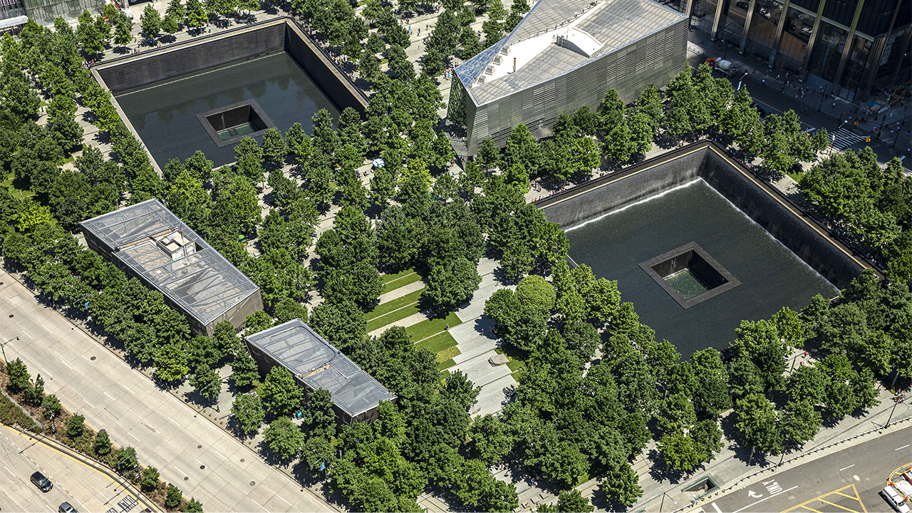 Memorial Plaza is seen from above in daylight. Dozens of oak trees fill the Plaza. These trees surround the two reflecting pools where the North and South towers once stood. Between the large, square pools is the Museum's glass and steel pavilion.