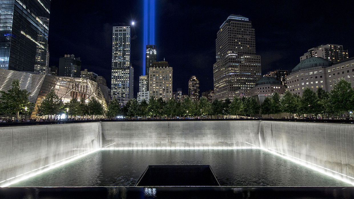 The blue lights from Tribute in Light shine over the illuminated memorial pool at night.