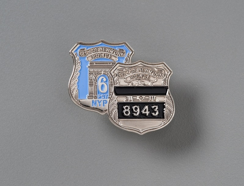 Two NYPD metal shield badges. One with the numbers '8943' written on black bar and the other with the number 6 written on light blue background.