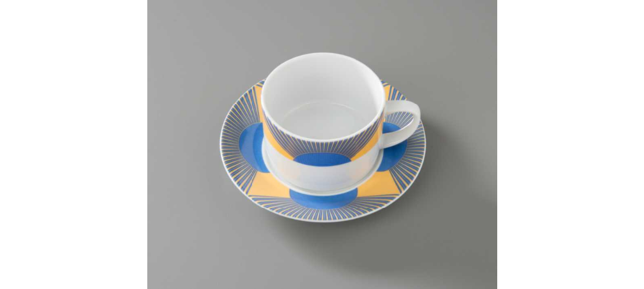 Coffee cup with matching saucer used at the Windows on the World restaurant. The yellow and blue graphic detailing resembles a rising sun, and the rays evoke the facade of the Twin Towers.