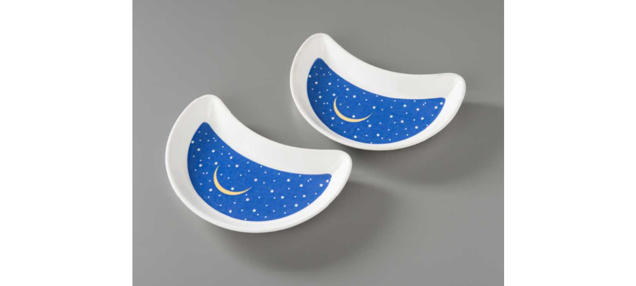 Crescent-shaped bread-and-butter plate used at Windows on the World restaurant. The face of the plate is blue with white stars and a yellow sliver moon.