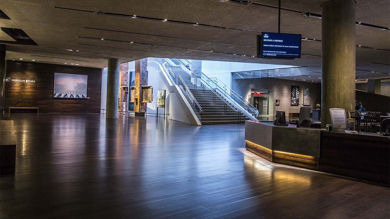 Sunlight pours down a large staircase into an empty Concourse Lobby. The light reflects off hardwood floors. An information desk is to the right and an illuminated image of the Twin Towers is off to the left.