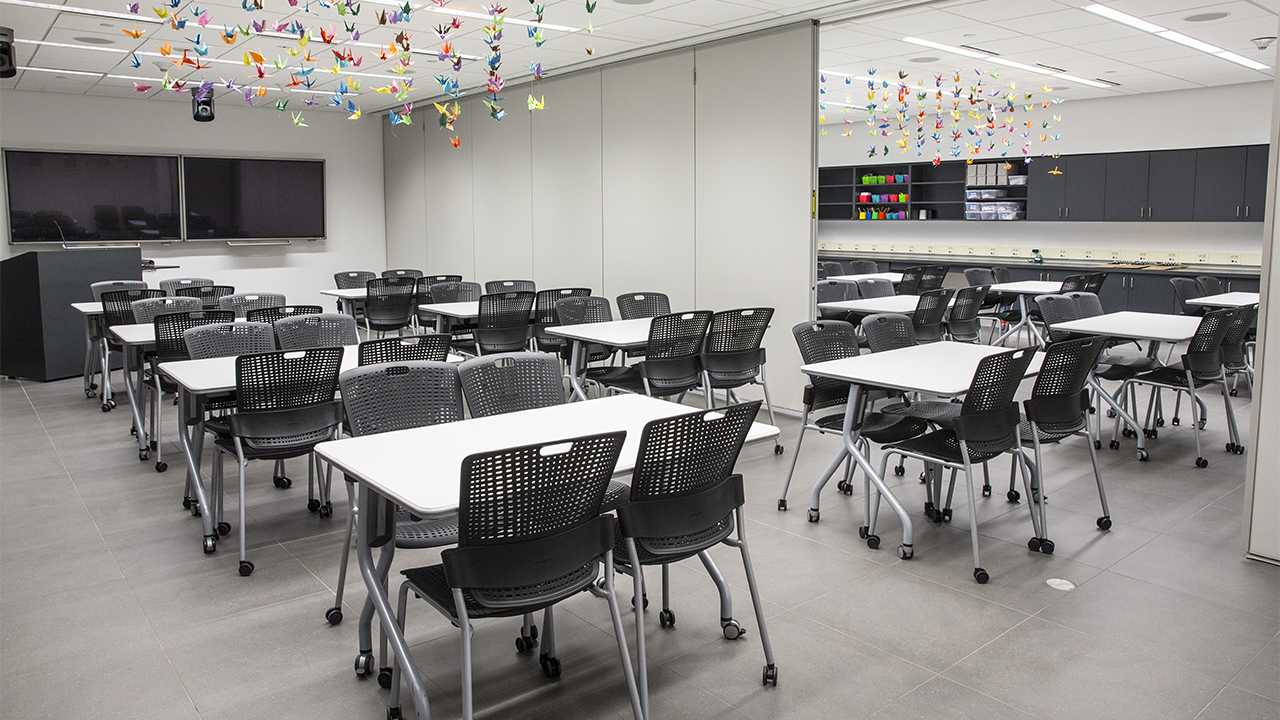 Black chairs and white tables fill an empty Education Center. There are two classrooms separated by a room divider. Colorful origami birds hang over the tables. Presentation screens and a lectern are at the front of the room.
