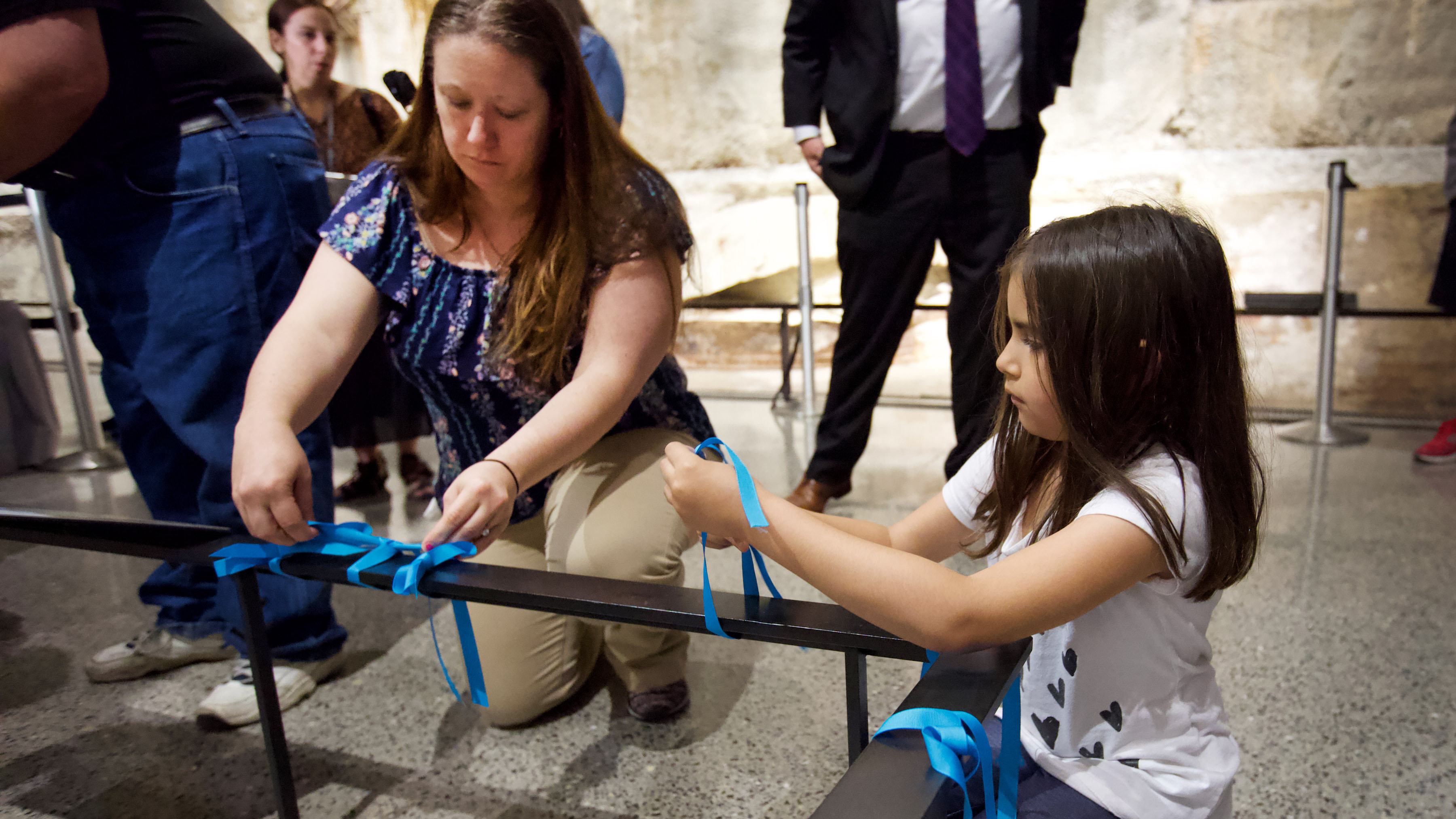 A woman and a young girl kneel down as they place blue ribbons on a black railing at the foot of the Last Column. Several other people stand behind them.