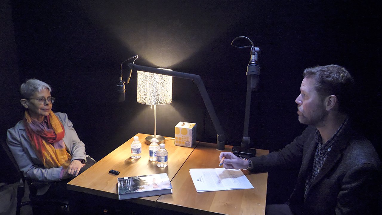 At a table in a dimly lit room, a woman with her hands on her lap sits across from a man with a pencil and paper. There is a lamp on the table and microphones are positioned in front of the man and woman.