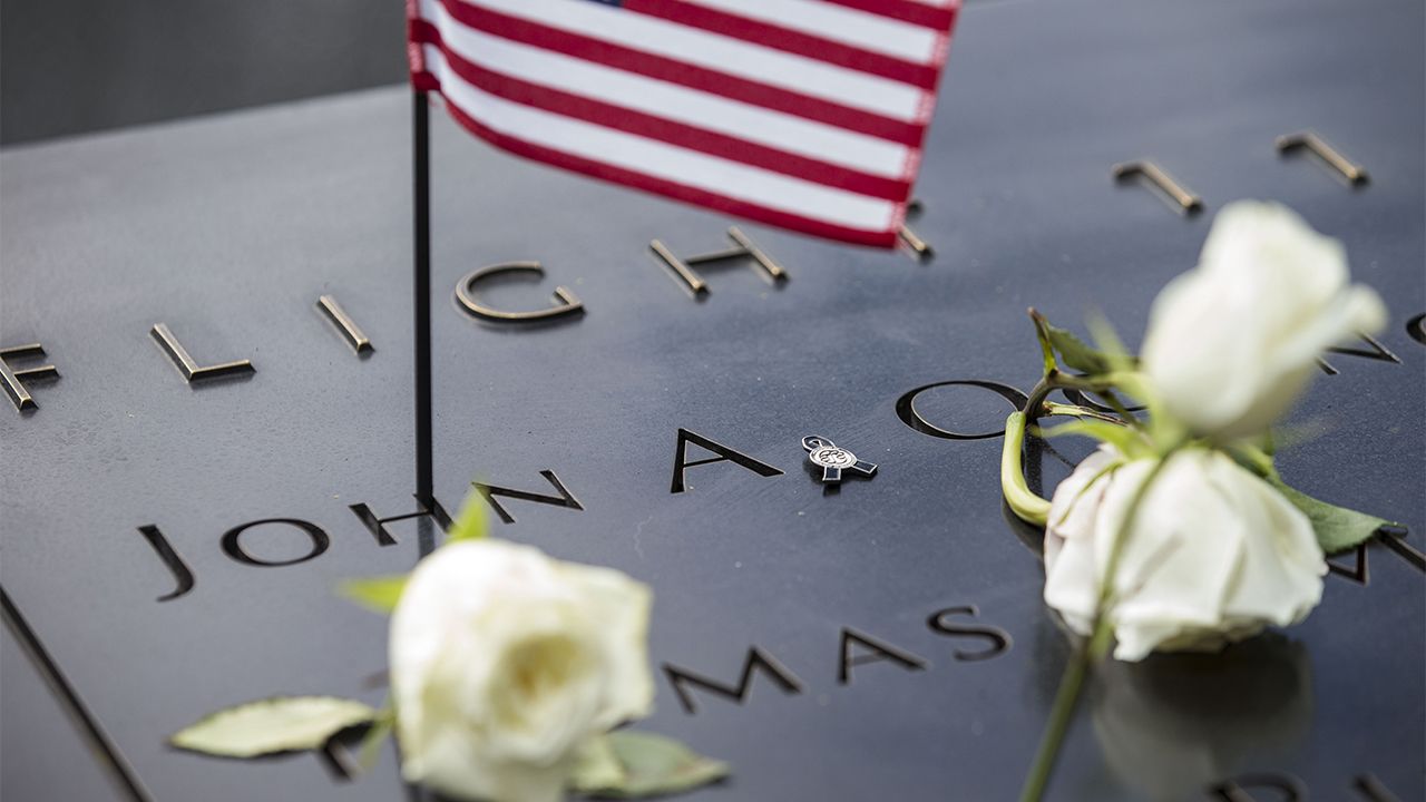 Several white roses and a small American flag have been placed at names on the Memorial. The names are under an inscription indicating they are American Airlines Flight 11 victims.