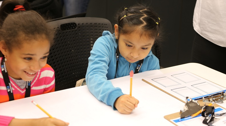 Two young girls sit at a white table and write on paper with pencils as they take part in a school program at the Museum.