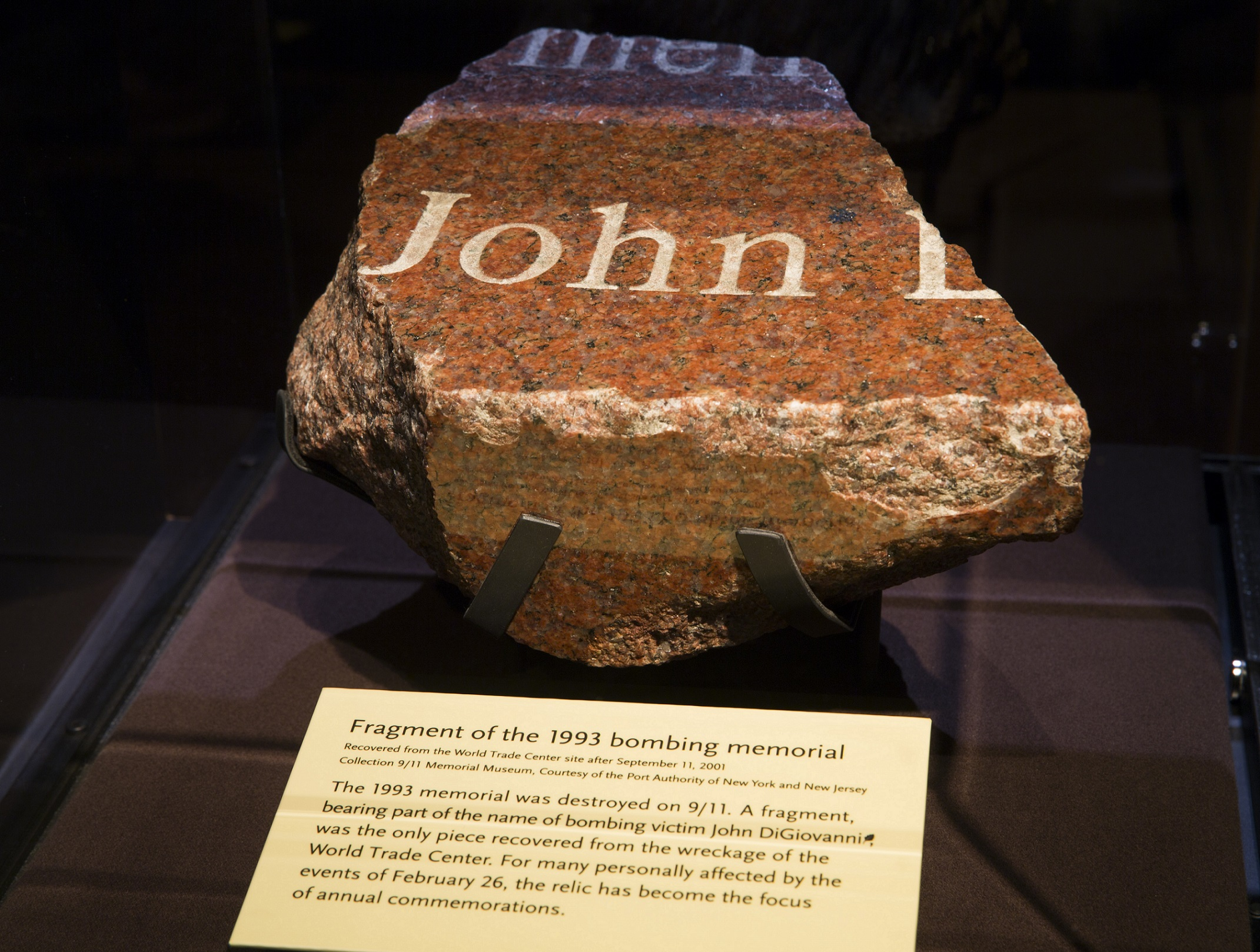 "A fragment from the original memorial to the victims of the February 26, 1993 bombing is displayed at the Museum. The name ""John"" can clearly be read on the piece of red, black, and white granite. A Museum placard below the fragment explains its historical significance."