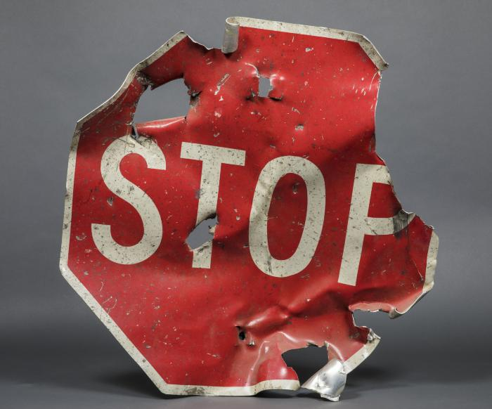 A red stop sign that was partially destroyed in the 1993 bombing of the World Trade Center is displayed on a gray surface at the Museum.