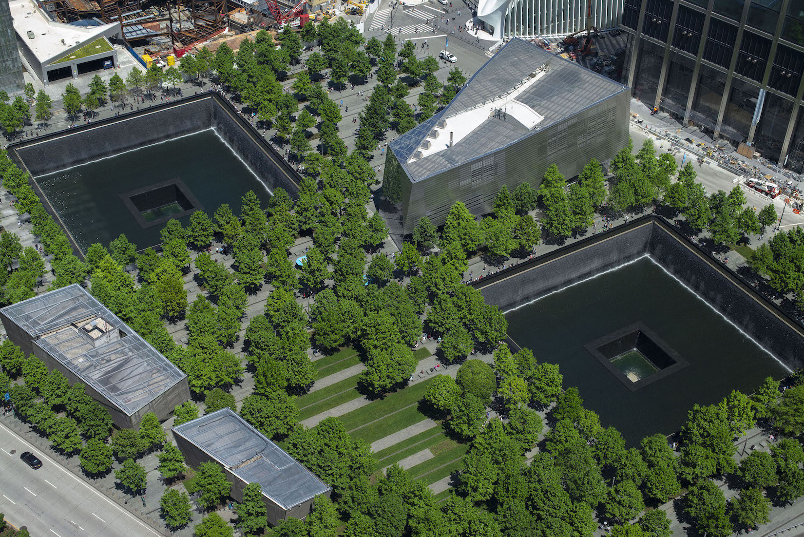Memorial Plaza is seen from above on a sunny day. Dozens of oak trees fill the Plaza with a vivid green. These trees surround the two reflecting pools where the North and South towers once stood. Between the large, square pools is the Museum's glass and steel pavilion.