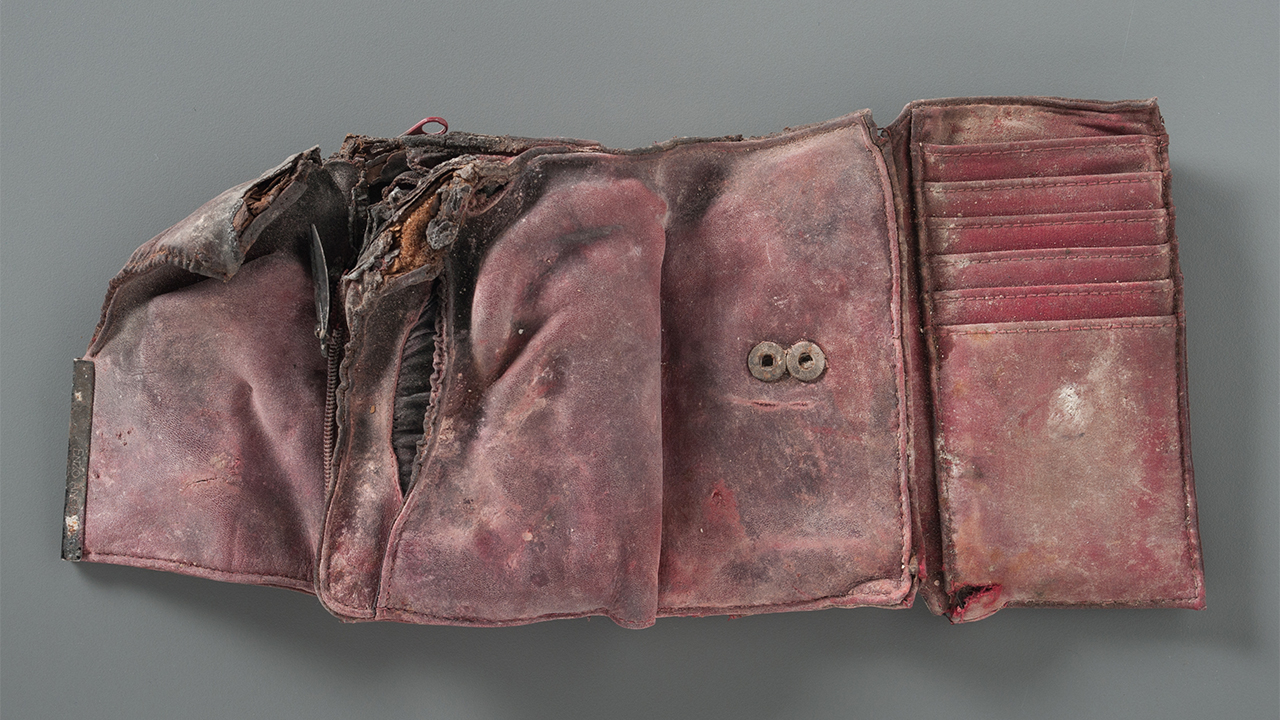 A damaged and stained red wallet from the Collection of the 9/11 Memorial Museum is open on a gray table. The wallet is empty. Its left corner is burned and ripped