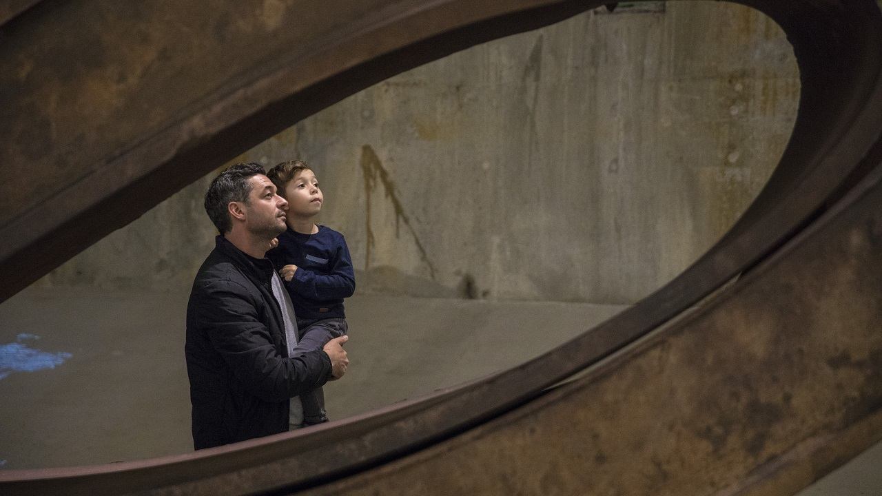 A man holds a boy as the two observe an object out of view in Foundation Hall. The two of them are framed by a piece of bent structural beam from the World Trade Center.