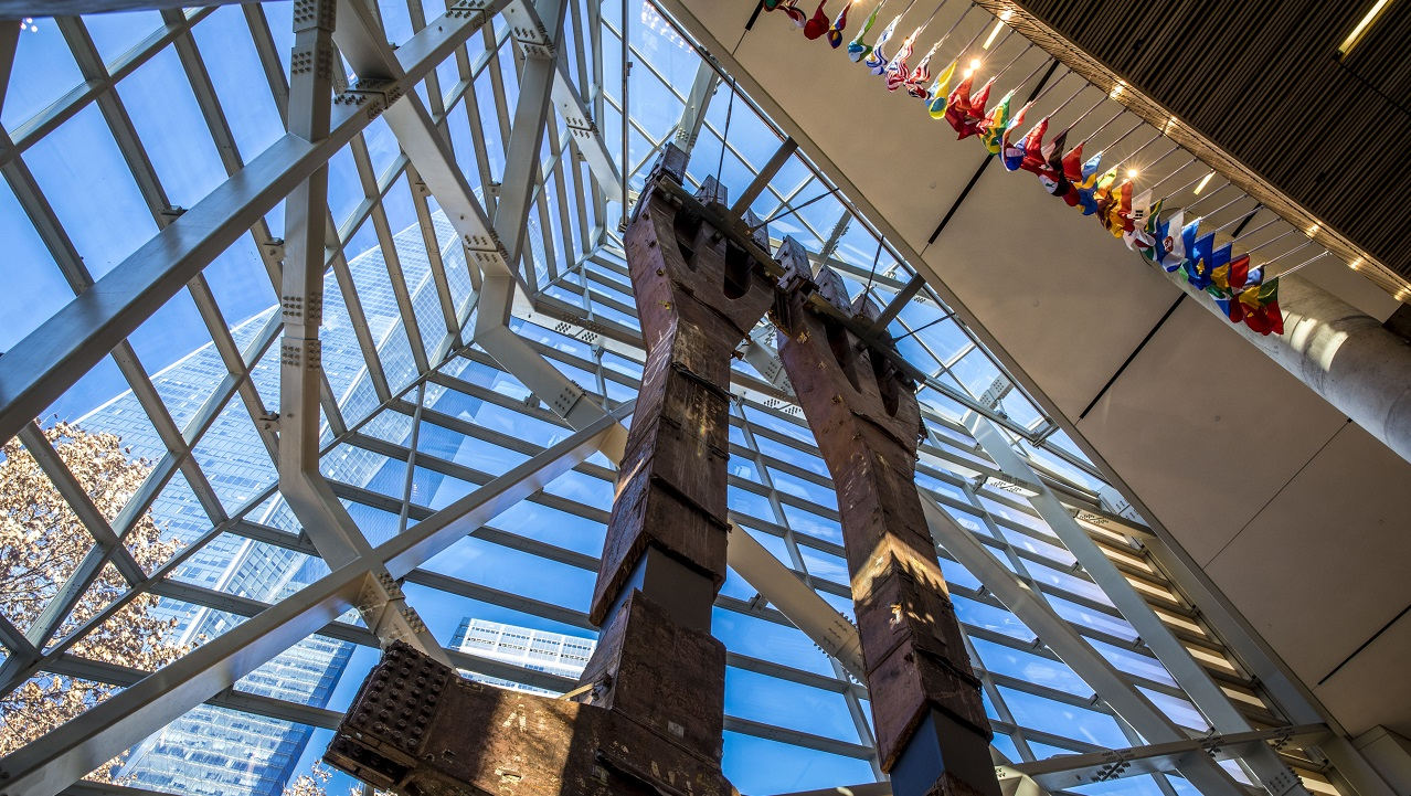 Two eighty-foot tall steel columns, known as the Tridents, tower over the interior of the museum Pavilion. One World Trade Center points skyward outside the windows.