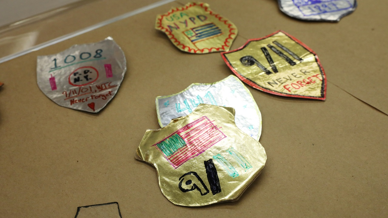 Children's craft projects show six first responder badges made of foil and paper. In the foreground, a badge made of gold foil shows an American flag with the date nine eleven written below it.