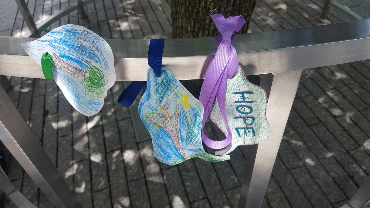 Three pieces of papers colored by children, cut into the shape of leaves, and tied with ribbons to a metal railing.