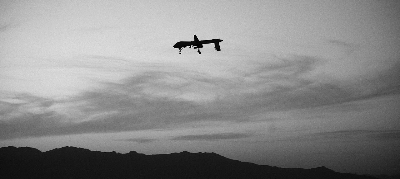 Silhouetted image of a drone in the sky flying over mountain tops.