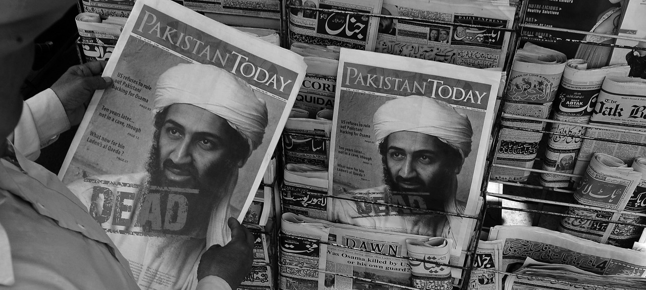 "Man holding 'Pakistan Today' newspaper. The front cover shows image of Osama bin Laden with word ""DEAD"" stamped on it."