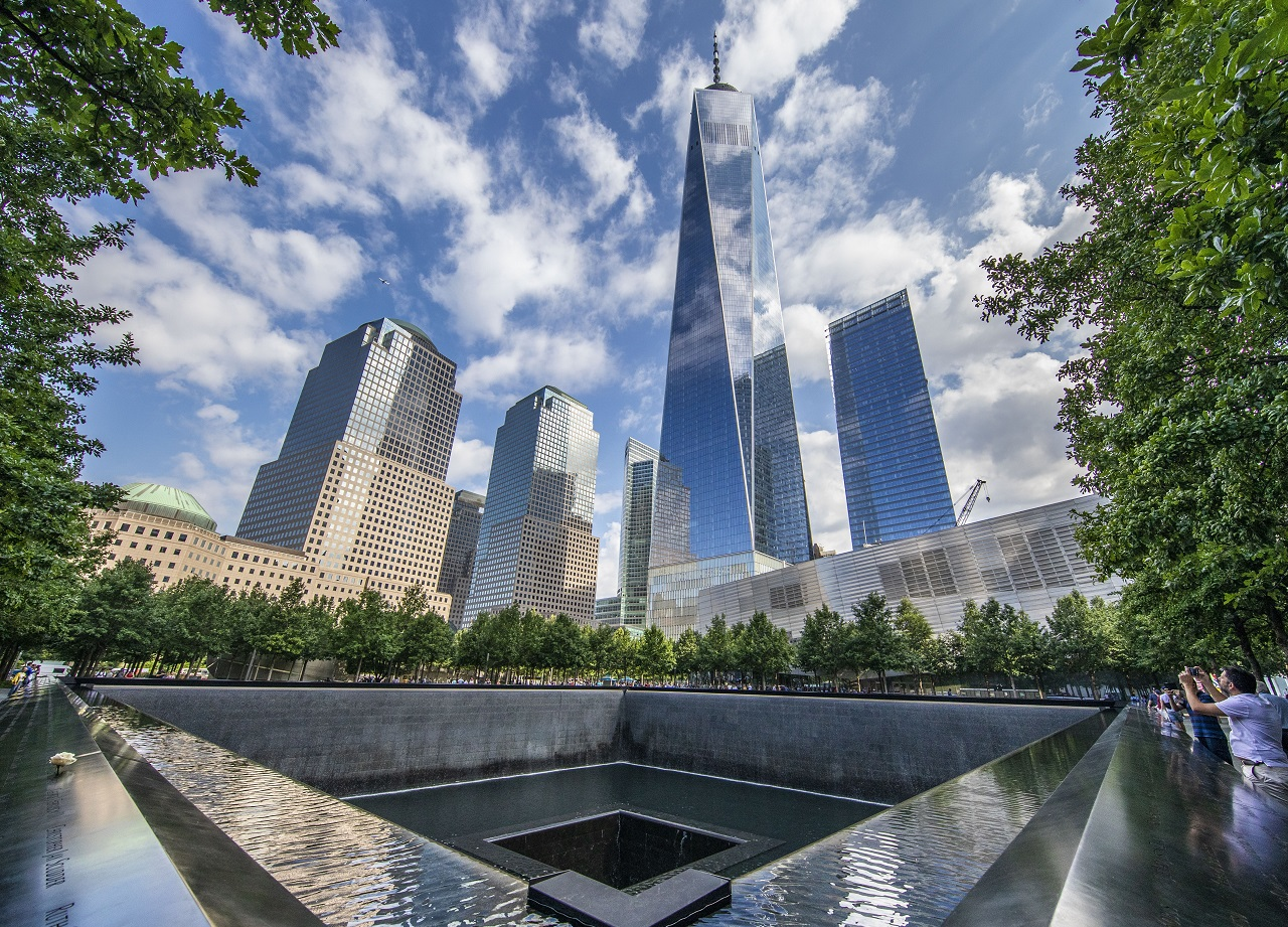 A view of the 9/11 Memorial on a partly cloudy day. Clouds are reflected in the facade of One World Trade.