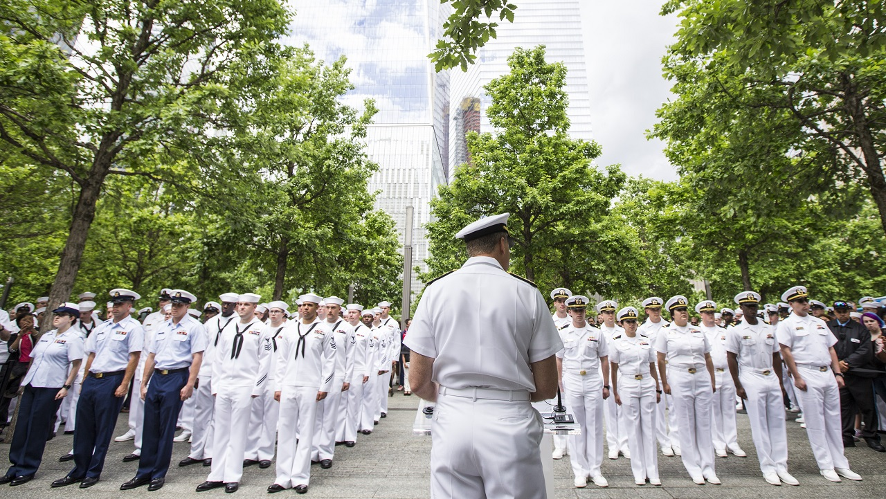 Dozens of U.S. Navy members dressed in white uniforms grouped in neat rows on the 9/11 Memorial plaza.