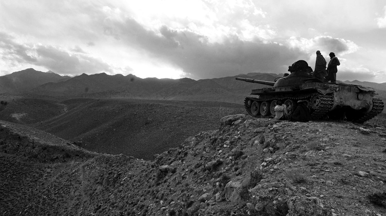 Two individuals standing on a tank overlooking a rocky desert landscape.