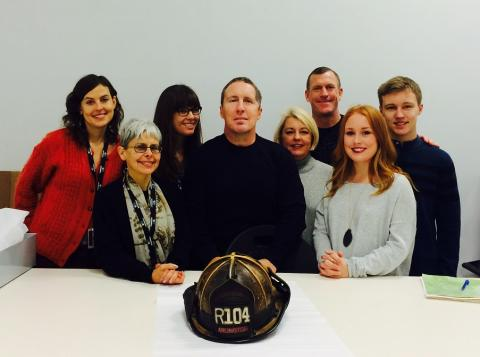 Retired Arlington County Fire Chief Robert Gray, members of his family, and curators from the Museum pose next to Gray's fire helmet, which Gray donated to the Museum.