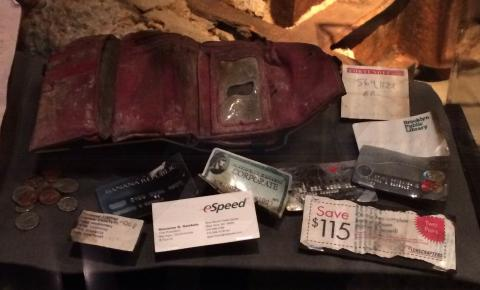 A wallet belonging to Giovanna Gambale is displayed at the Museum. The red wallet is heavily damaged and stained with dirt. The contents of the wallet, including credit cards, coupons, note paper, and coins have been laid out in front of it.