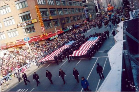 Emergency responders carry two American flags in the shape of the Twin Towers at the 2001 Thanksgiving Day Parade in Manhattan. Hundred watch them from the sidewalks.