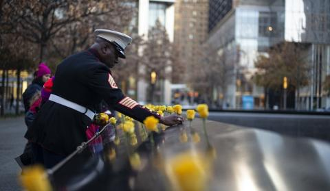 A Medal of Honor recipient in dress uniform places yellow roses on the 9/11 Memorial parapets.