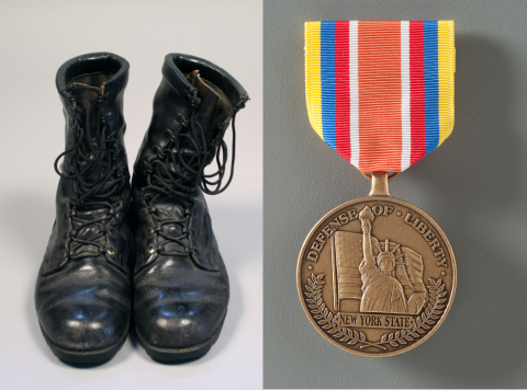 "A composite image shows a pair of black leather combat boots. The boots are polished but well worn, and the leather is cracking in places. Next to the boots is a medal depicts an American flag and the Statue of Liberty with raised text: ""DEFENSE OF LIBERTY 