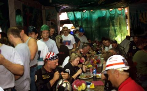 In this archival photo, rescue and recovery workers sit for a meal or line up to get their food in an informal restaurant with a green tarp for a door.