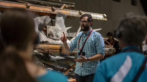 A bearded young tour guide, standing in front of a mangled segment of an antenna recovered from the World Trade Center, gestures as talks to visitors on a tour of the 9/11 Memorial Museum.