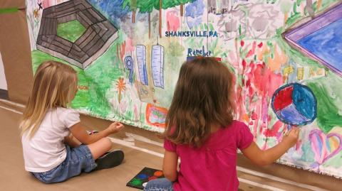 Two young girls, their hair reaching past their collars, are seen from behind as they add to a colorful hand-drawn mural honoring the victims of 9/11 in the art-making activity in the 9/11 Memorial Museum's Education Center.
