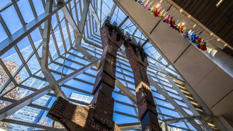Two eighty-foot tall steel columns, known as the tridents, tower over the interior of the Museum pavilion. One World Trade Center stretches skyward outside the Museum windows.