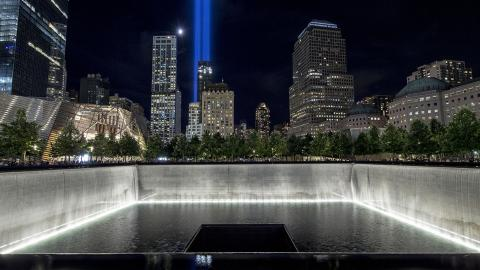 In this nighttime photograph, the South Pool of the 9/11 Memorial is shown in the foreground as the twin beams of the Tribute in Light shine over the buildings of lower Manhattan.