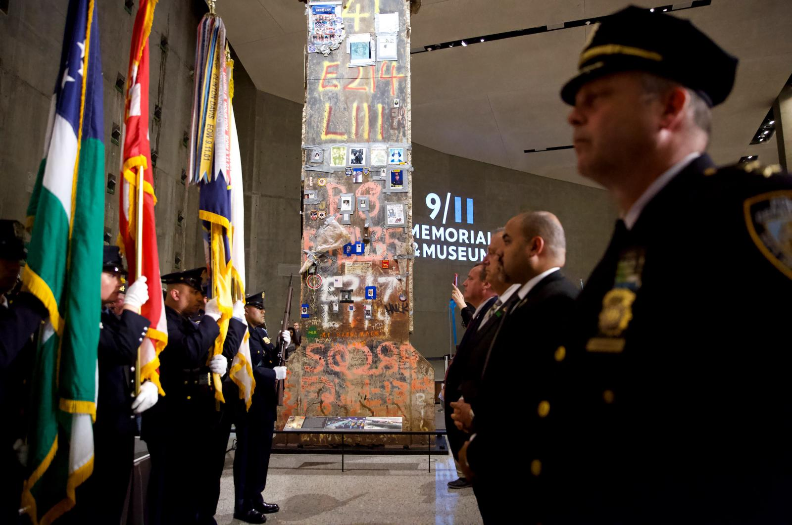 The Last Column towers over NYPD flag bearers standing to the left and men in suits and ties standing to the right. The Last Column, a fixture of Foundation Hall, is covered in photos and written tribute to rescue and recovery workers.