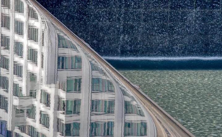 In a close-up view, a building reflects off the 9/11 Memorial as water cascades down into a reflecting pool.