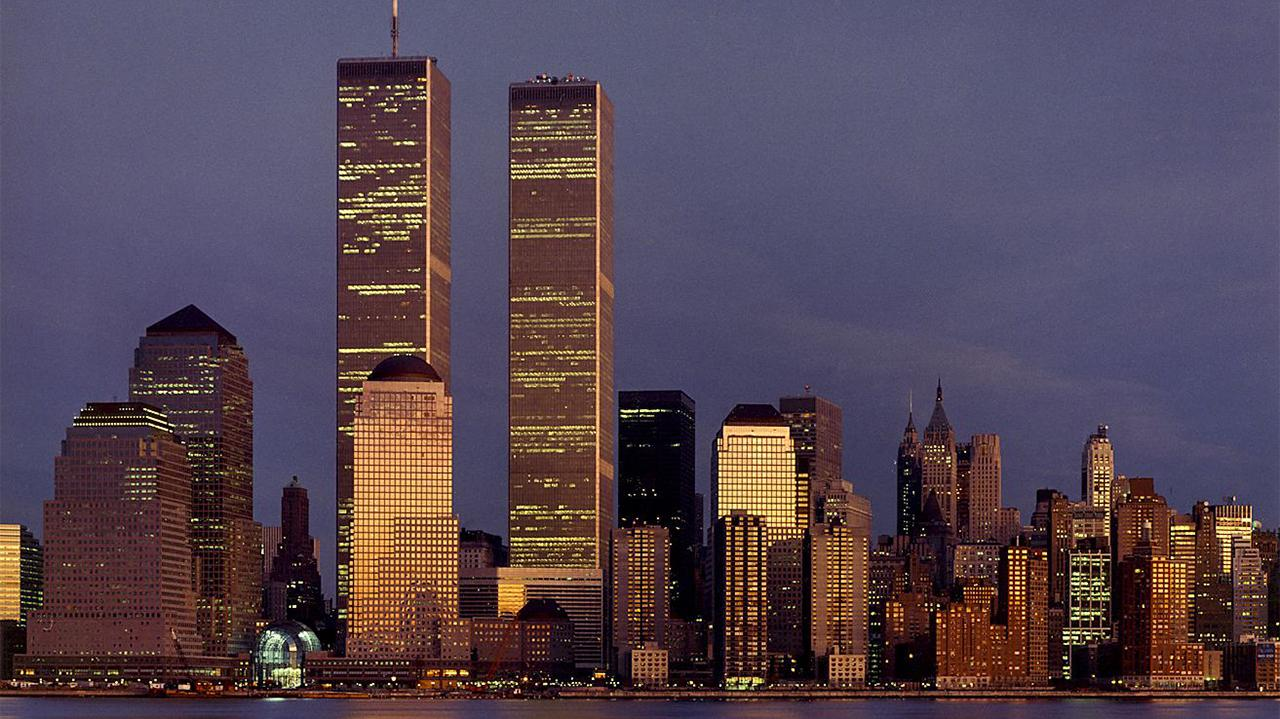 The Twin Towers dominate the skyline of lower Manhattan at dusk. An orange sunset reflects off of them and surrounding skyscrapers. The sky is a dark blue with a streak of clouds.