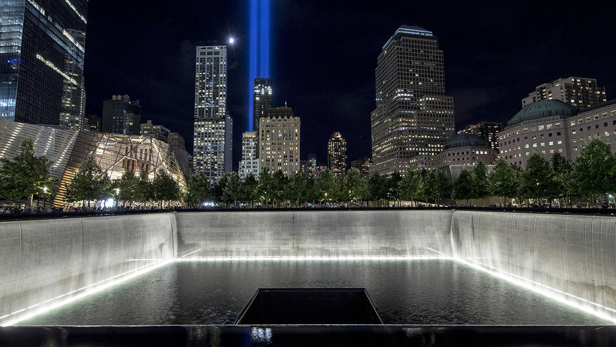 Water cascades down the illuminated walls of the North Tower reflecting pool on a warm night. The water pours down a square hole at the center of the pool. In the distance, a moon hangs over the city and the Tribute in Light shines above the buildings.